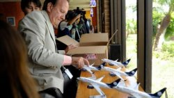 """In this July 15, 2011 photo, Michael Jones, the business development manager at Brownsville South Padre Island International Airport in in Brownsville, Texas, lays out a series of model Aeromexico planes to be given to dignitaries upon the arrival of Aeromexico's first direct flight to the airport from Monterrey, Mexico. (AP Photo/The Brownsville Herald, Paul Chouy)"""