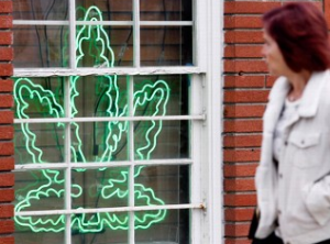 A pedestrian walks past a marijuana leaf neon sign advertising a medical marijuana provider along a street in the Sherman Oaks section of Los Angeles. (Photo by Richard Vogel)