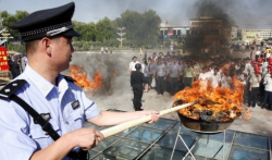 A Chinese policeman lights a cauldron filled with illicit drugs.