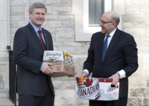 Harper collecting on a cross border beer swap from a hockey bet with fellow drinker Obama.