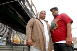 Maximo Colon, left, and his brother Jose stand in front of a bar in the Queens borough of New York where they were arrested in a drug raid. (AP Photo/Henny Ray Abrams)