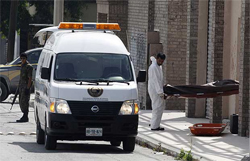 Forensic workers remove one of three bodies slain at an abandoned warehouse in the suburb of Guadalupe in Monterrey, northern Mexico, April 8, 2009.