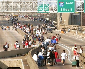 Evacuees walk on the elevated freeway in downtown New Orleans