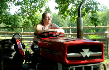 laurie-maceachern-shown-on-her-tractor-outside-her-little-p