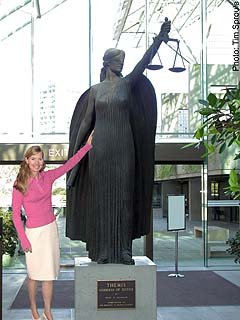 Michelle Kubby stands next to statue of Themis