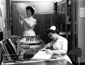 Nurses preparing drug dosage and recording data