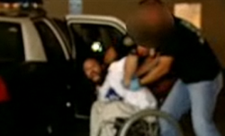 San Diego police force a man out of his wheelchair and into the back of a police car.