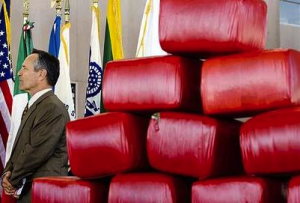 U.S. border czar Alan Bersin, with bales of marijuana, appears at a news conference May 27, 2009 at a crossing between San Diego and Tijuana. (Photo: Carlos Osorio)