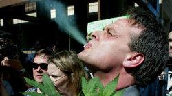 Cannabis crusader Marc Emery, of Vancouver, smokes marijuana as he holds a plant at a gathering of pro-marijuana legalization supporters outside police headquarters in Toronto.