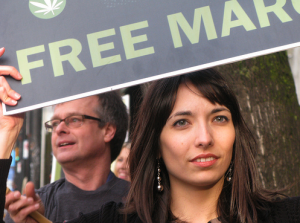 Pot activists Jodie and Marc Emery hold signs along the Olympic Torch route outside Cannabis Culture Headquarters in Vancouver. (Photo by Jeremiah Vandermeer)