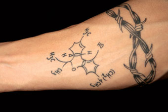 Mik Mann of Opus Pharms: tattoo on arm, THC molecule structure by Shelly Fox at 5 Star Tattoo Company in Port Alberni, BC