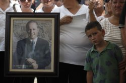 A child stands next to a picture of Edelmiro Cavazos, mayor of the tourist town of Santiago, during a public ceremony downtown in the municipality of Santiago, some 30 km (18.6 miles) from Monterrey August 19, 2010. Mexicans carrying candles and flowers paid tribute on Thursday to a mayor killed by drug hitmen, while officials vowed a tough response to increasingly bold cartels but resisted calls for more troops