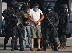 Suspected member of the Gulf Cartel Gregorio Sauceda Gamboa and police wear face masks as a precaution against swine flu during his arrest. (AP Photo/Marco Ugarte)