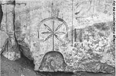 Ancient wall carving of the Goddess Seshat, with her pot-leaf symbol over her head.